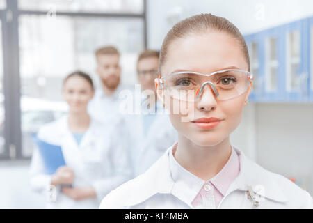 Close-up portrait of young woman scientist in lab coat and protective goggles smiling - Stock Photo
