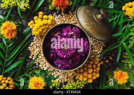 Brass Container with Purple Chrysanthemum Flowers on Ginger Spill - Stock Photo