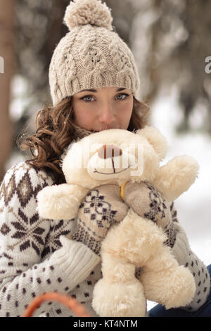 Beautiful, nice, smiling,little and wearing sweater hut and mittens and little girl with a teddy bear in winter - Stock Photo