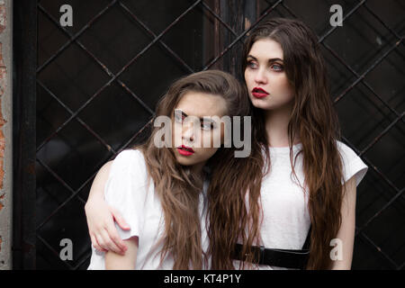 Two scared frightened horror girl in white dressing gown looking aside. Theme Halloween. Dark picture of two beautiful - Stock Photo
