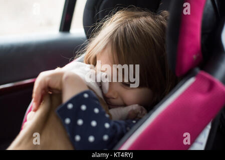 A toddler girl hugging a six week old puppy while sitting in a car seat. - Stock Photo