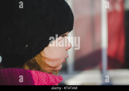 Close up of a toddler's face wearing a winter hat. - Stock Photo
