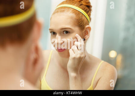 Redhead girl applying beauty cream in home bathroom at morning. Young woman taking care of her skin, looking at - Stock Photo