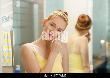 Redhead girl applying beauty cream in home bathroom at morning. Young woman taking care of her skin, looking intimately - Stock Photo