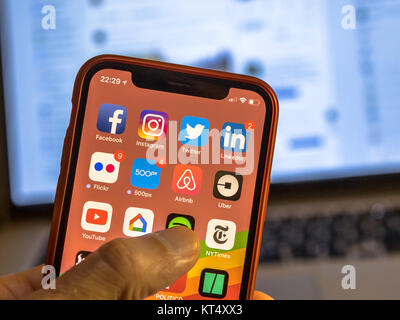 NEW YORK, USA - NOVEMBER 7, 2017: Social media app icons on new smartphone display close-up around other iOS applications - Stock Photo