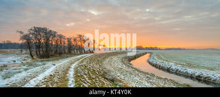 Meandering River in Frozen grassland landscape on early morning with rising sun under beautiful sky - Stock Photo