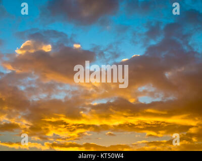 Clouds on fire in beautiful clouded sky at sunrise - Stock Photo
