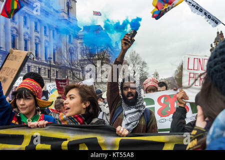 A man in the Global Frontline bloc holds a blue smoke flare as they go down Whitehall past the Foreign and Commonwealth - Stock Photo