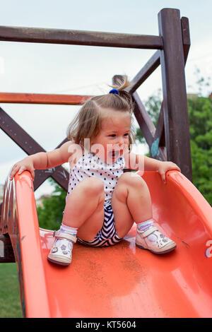 smiling girl sliding down on slide at playground - Stock Photo
