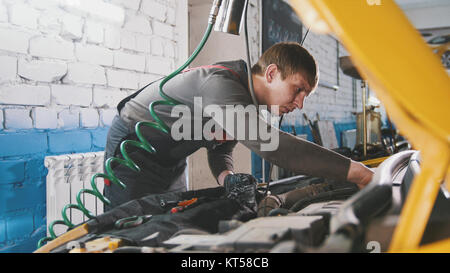 Mechanic in car repairing service - diagnostics in engine compartment - Stock Photo