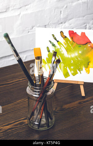 close-up view of various paint brushes in glass and abstract painting behind at designer workplace - Stock Photo