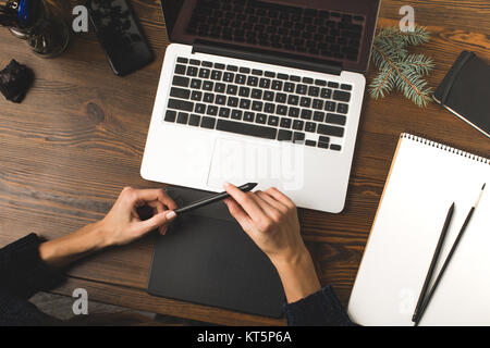 partial view of designer using graphics tablet and working with laptop at workplace  - Stock Photo