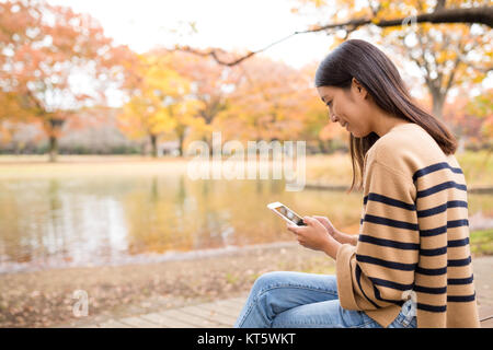 Woman using cellphone at autumn fall tree park - Stock Photo