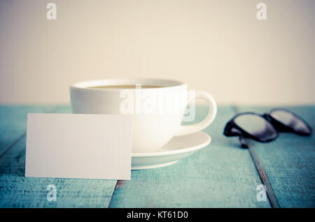 Blank business cards, cup of coffee and eyeglasses on blue wooden table. - Stock Photo