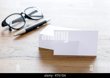 Blank business cards, pen and eyeglasses on table. - Stock Photo