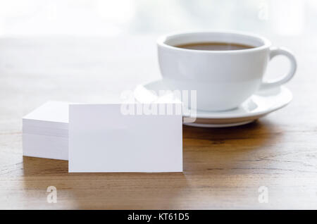 Blank business cards and cup of coffee on wooden table. - Stock Photo