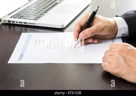 Close-up man signing of on resume form. - Stock Photo