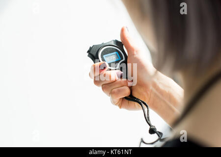 back view of sporty woman holding stopwatch in hand - Stock Photo