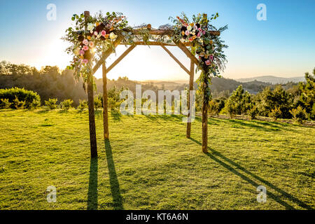 Jewish traditions wedding ceremony. Wedding canopy chuppah or huppah with the sun behind it - Stock Photo