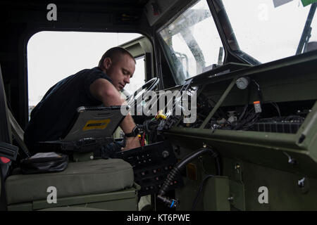 CAMP FOSTER, OKINAWA, Japan – Cpl. Ryan Simmons tests the electrical components of a dashboard in a wrecker Dec. - Stock Photo