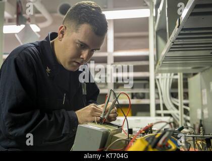 ATLANTIC OCEAN (Dec. 9, 2017) Aviation Electronic's Technician 2nd Class Justin Milligan troubleshoots a radar altimeter - Stock Photo