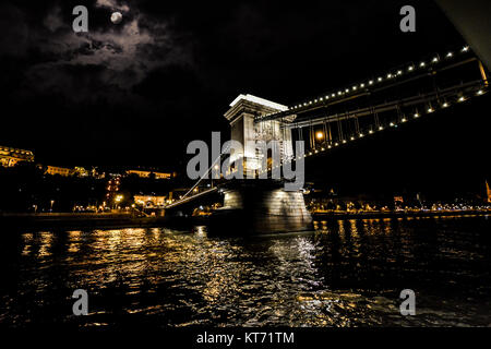 City lights of Budapest from the Danube River under a full moon and with the Chain Bridge lit up at night - Stock Photo