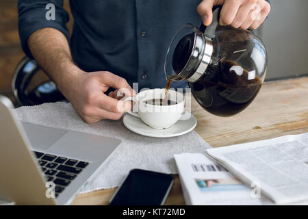 Partial view of man pouring coffee in cup on desk with laptop and smartphone - Stock Photo