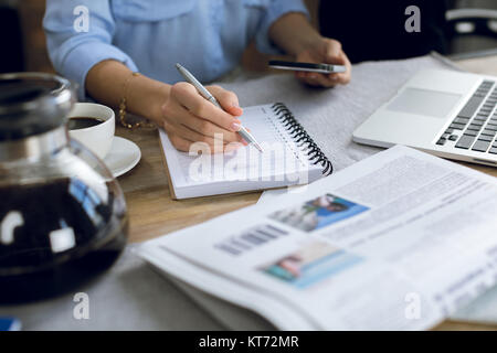 Close-up partial view of woman taking notes while using smartphone - Stock Photo