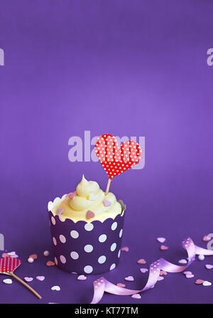 Vanilla cupcake with small decorative hearts and red heart topper, in violet baking paper cup, against violet background - Stock Photo