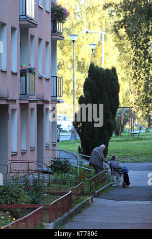 old man wheeling a women in wheel chair out of a house - Stock Photo