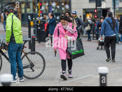 Young Asian woman dressed in expensive looking clothing in Winter, in the busy city of Brighton, East Sussex, England, - Stock Photo