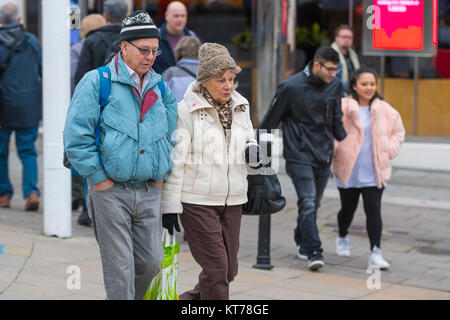 Senior couple walking through a city shopping, dressed in hats and coats in Winter in the UK. - Stock Photo