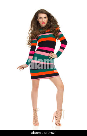 Beautiful young woman in colorful striped mini dress and high heels is posing with blown hair and looking at camera. - Stock Photo