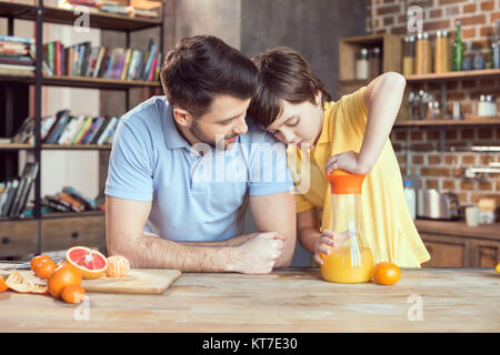 Father and son squeezing fresh orange juice at kitchen table - Stock Photo