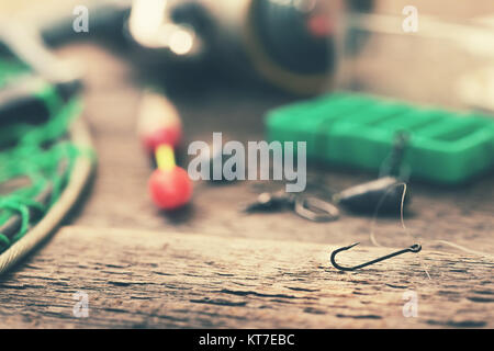 fishing hook and other equipment on old table - Stock Photo