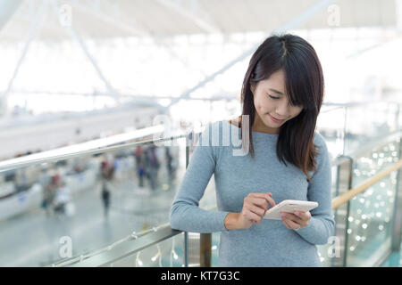 Woman using mobile phone at airport - Stock Photo