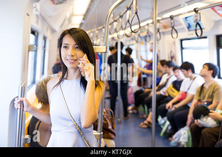 Woman talking on cellphone inside train compartment - Stock Photo