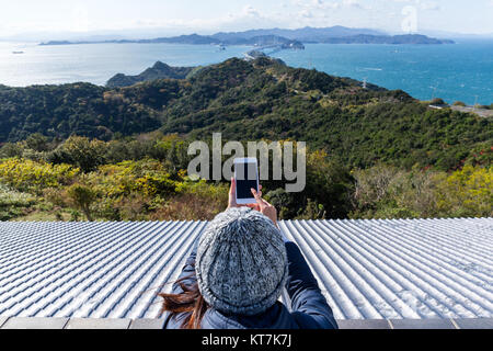 Woman using mobile phone to take photo - Stock Photo