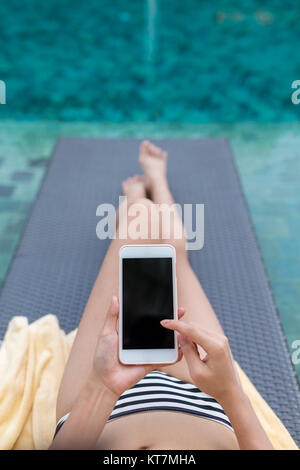 Woman relax on sunbath in swimming pool with using mobile phone - Stock Photo