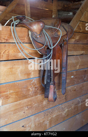 Western saddle on stable wall at Bar U Ranch National Historic Site - Stock Photo