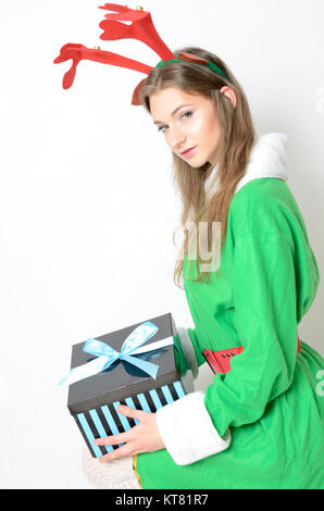 Young female model, Christmas photo session. Twenty years old girl in reindeer costume. - Stock Photo