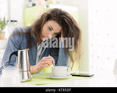 Tired lazy woman having breakfast at home in the kitchen, she is stirring coffee - Stock Photo