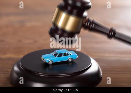 Gavel Striking On A Car Model - Stock Photo
