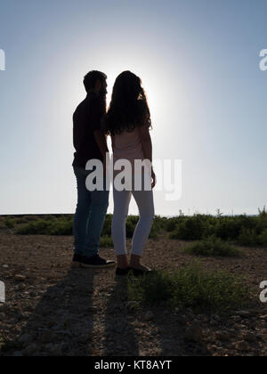 Rear view of a young couple standing outdoors - Stock Photo