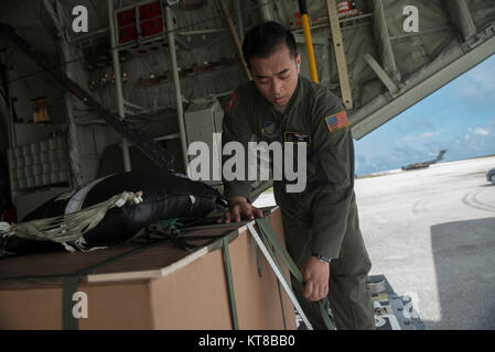 Staff Sgt. Joseph Arcega, a loadmaster with the 36th Airlift Squadron, checks the rigging of an airdrop bundle during - Stock Photo
