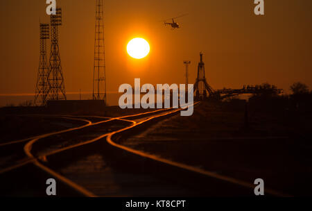 A security helicopter is seen surveying the launch pad area ahead of the Soyuz TMA-16M spacecraft arrival by train, - Stock Photo