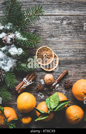 Clementines, fir tree, spices and snow on old wooden background. Christmas winter composition - Stock Photo