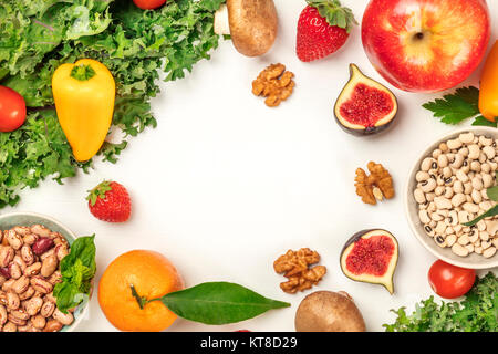 Vibrant fresh vegetables, fruits, cereals, and mushrooms on white background with copyspace - Stock Photo
