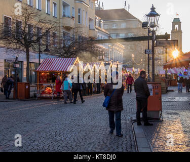 Berlin Spandau People enjoy typical Traditional German Christmas market stalls in cobbled Old Town Street - Stock Photo