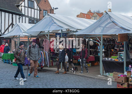 People with shopping bags walk past stalls (1 selling clothes) in Shambles Market, an historic market area in York - Stock Photo
